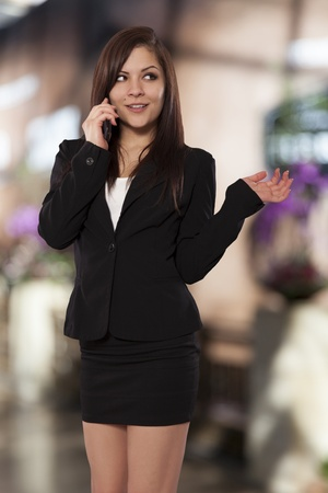 Beautiful young woman in form fitting business clothes has a phone conversation