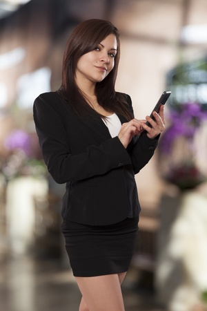 coy: Beautiful business woman flashes a coy smile while using her phone