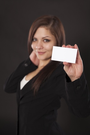 Beautiful business woman holds out a business card isolated on a dark background  Stock fotó