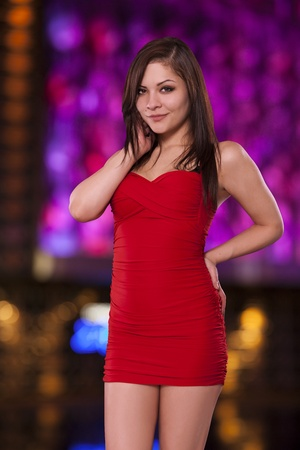 Pretty woman in a red dress poses with confidence in front of city lights