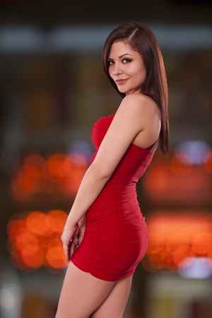 tight fitting: Young woman dressed for the clubs, smiles and poses in front of city lights