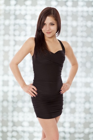 confidently: Beautiful woman smiles confidently in a little black dress  Stock Photo