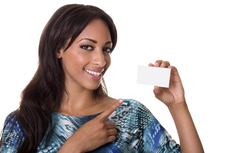 Beautiful woman in a colorful top points to a blank business card