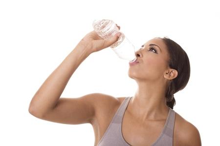 sediento: Una mujer sacia su sed después de un duro entrenamiento