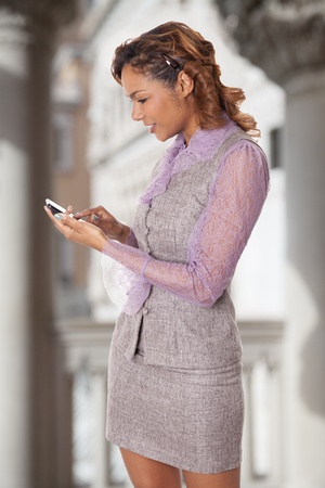 hour glass figure: Mixed race woman interacts with her cell phone