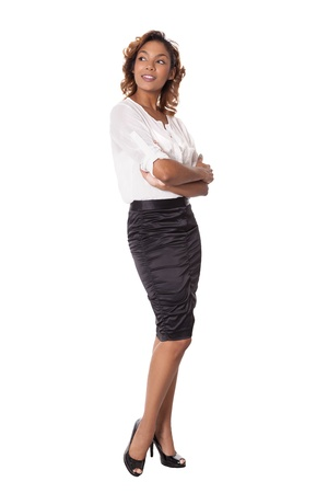 Elegant woman in a black skirt looks at an object to her side, isolated on white background  Stock Photo