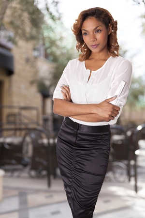 hour glass figure: Beautiful woman in a black skirt and white blouse stands with arms folded