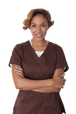 Fresh faced woman stands with arms crossed in scrubs, isolated on white background  Stock Photo