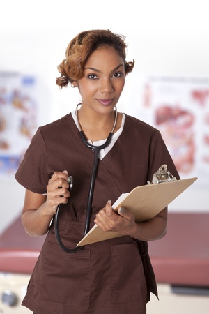 Pretty woman in scrubs holding charts and a stethoscope  Stock fotó