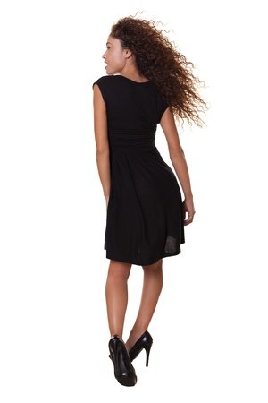 dynamically: Beautiful Latin woman in a little black dress moves dynamically as the wind blows her thick hair   Stock Photo
