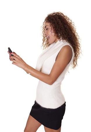 Trendy young woman is surprised by something on her cell phone, isolated on a white background   Stock fotó
