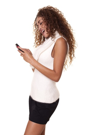 Fashionable woman smiles while using her phone isolated on a white background