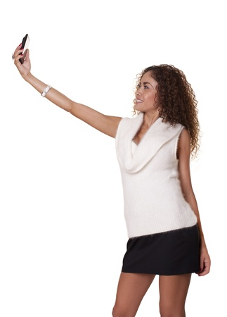 Happy woman takes a picture of herself with her phone, isolated on a white background