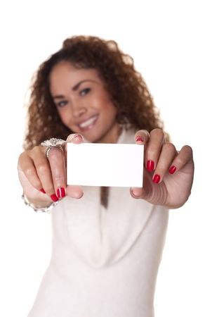 Latin businesswoman holds out a blank business card isolated on white background