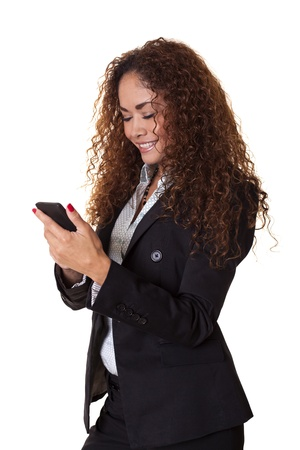 Happy woman in a business suit smiles while using her phone isolated on a white background
