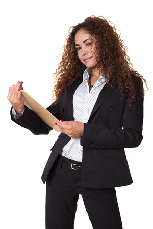 Latin woman in business attire stands smiling with a clipboard