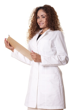 Female physician stands, smiling with a clipboard, isolated on white background