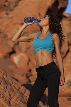 Very toned Latin woman drinks water from a bottle in the desert  Stock fotó