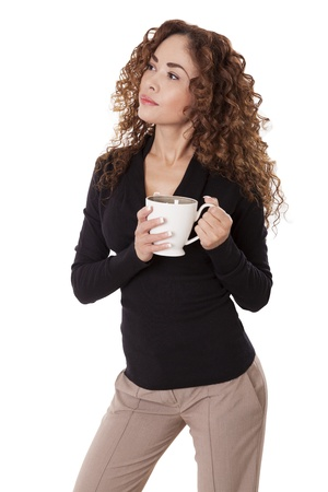 Pretty woman looks to the side with a coffee cup held up near her chest, isolated on white background  Imagens