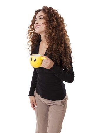 Woman with thick, curly hair laughing while holding a yellow coffee cup, isolated on white background