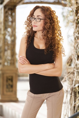 progressive: Attractive young woman with glowing sking stands with arms crossed