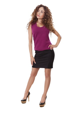 Woman in little black skirt and heels, looks at something next to her, isolated on white background  Stock fotó