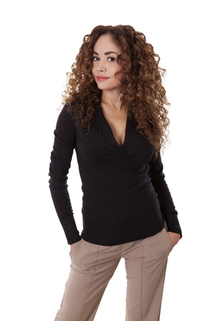 Woman with thick, curly hair standing with her hands in her pockets, isolated on white background