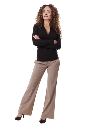 Woman with thick, curly hair standing with her arms crossed, isolated on white background