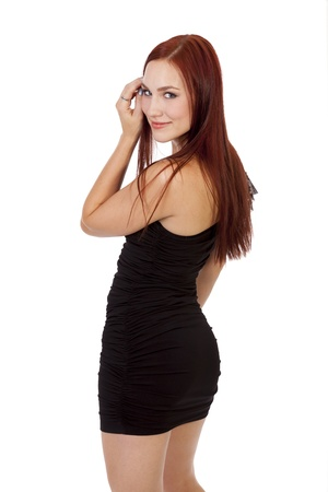 Pretty young woman in a little black dress smiles flirtatiously and looks over her shoulder Stock fotó - 40661184