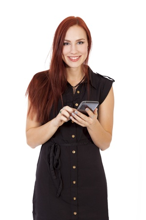 Pretty young woman in a blue dress smiles while using a smart phone
