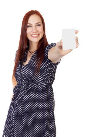 hottie: Pretty young woman with long red hair smiles and holds a business card vertically  Stock Photo