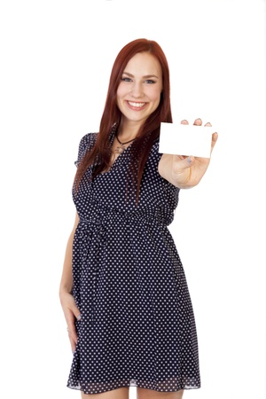 A young woman with long red hair smiles while holding a business card out in front of her