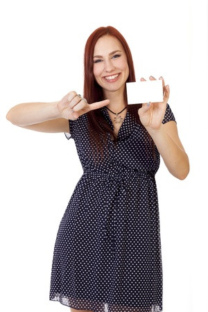 tight fitting: Pretty young woman with long red hair smiles and points to a blank business card  Stock Photo