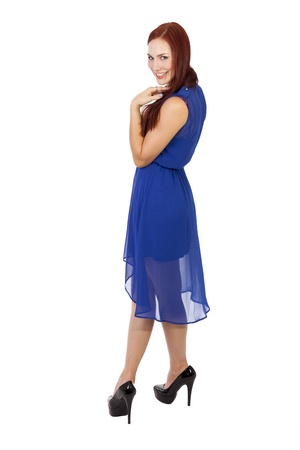 Full length portrait of a happy woman with red hair in a blue dress