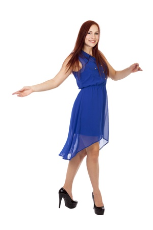 Pretty young woman with long red hair smiles and twirls in a blue dress