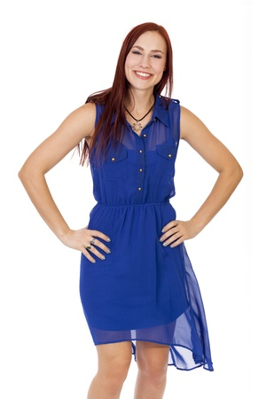 Attractive young woman with long red hair flashes a big smile withe her hands on her hips