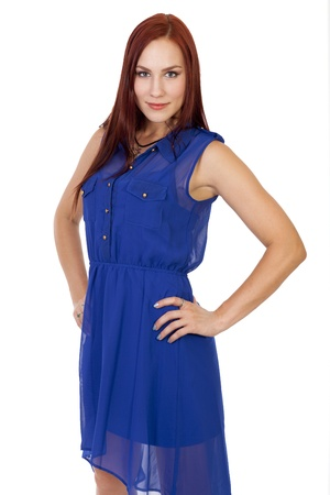 confidently: Pretty young woman with long red hair poses confidently with a slight smile  Stock Photo