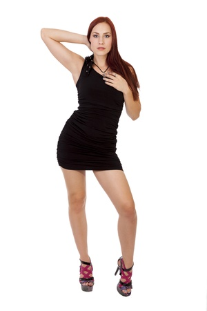 Pretty young woman with long red hair poses in a black dress