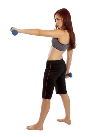 capri pants: Pretty woman with red hair holds a hand weight out in front of herself