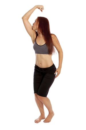 capri pants: Pretty fitness model with red hair kisses her flexed arm