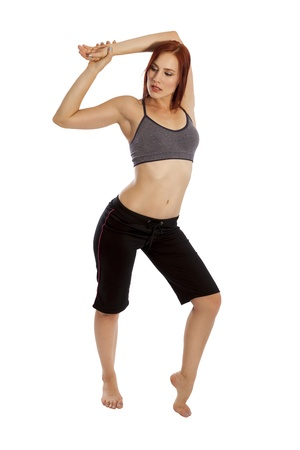 capri pants: Pretty woman with red hair stretches her arms before a workout