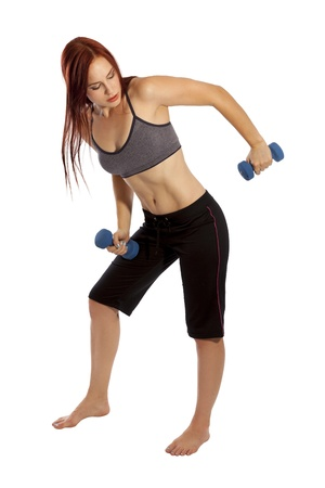 Pretty woman with red hair works her triceps with hand weights