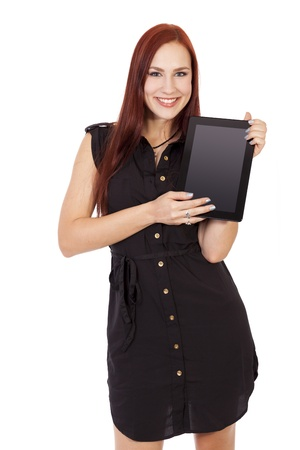 Pretty young woman in a blue dress smiles while holding a blank tablet computer
