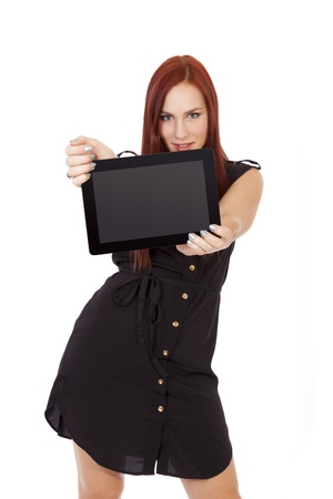 A happy young woman with long red hair smiles while holding a tablet computer  Stock fotó
