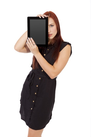 Pretty young woman with long red hair blocks part of her face with a blank tablet computer