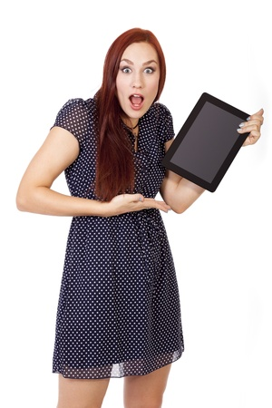 hottie: Pretty young woman with long red hair looks shocked at what is on the screen of her tablet computer  Stock Photo