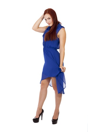 tugging: Pretty young woman touches her long red hair while tugging at her dress
