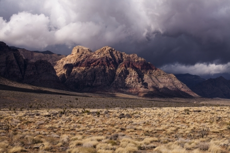 A nasty winter storm brews over colorful Red Rock, Illuminated by the sun  photo