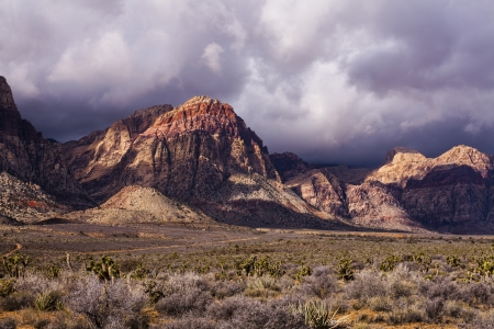 Storm clouds scrape across the peaks of colorful tan and red mountains  photo