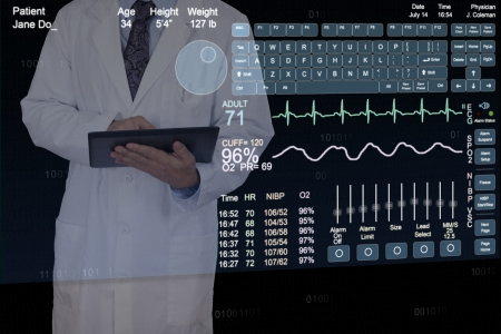 A Physician uses a tablet computer while standing behind a floating computer display  Stock Photo - 23283605